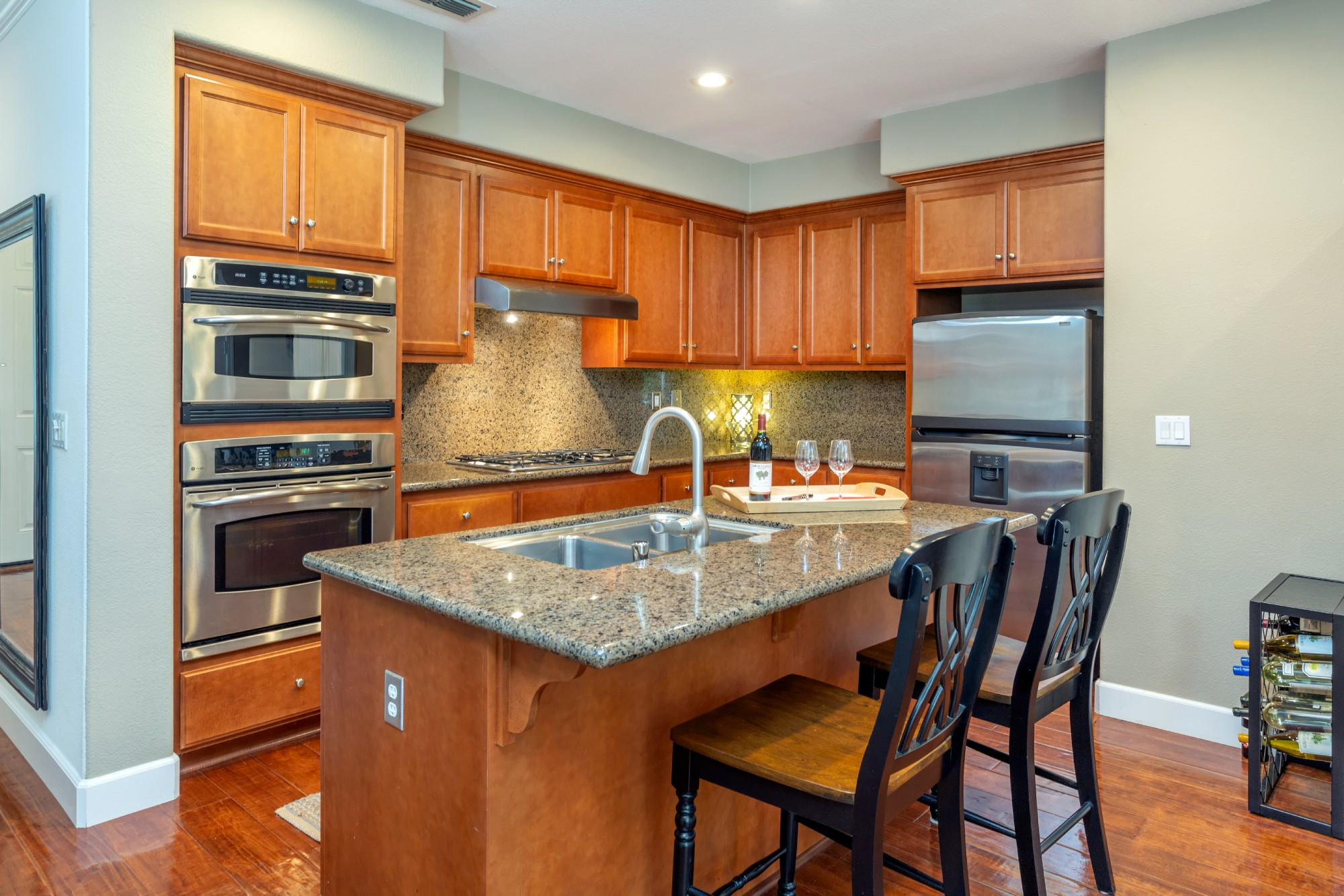 Kitchen amenities include built-in stainless oven and microwave, gas stove top and dishwasher.  Lovely granite slab graces the counters and island